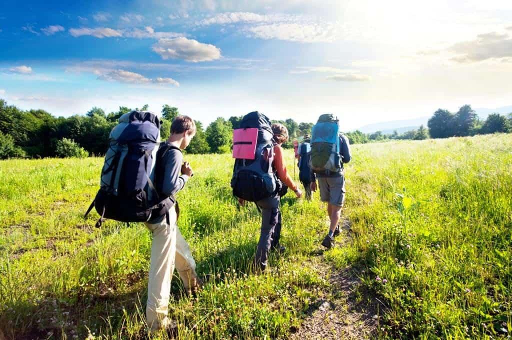 Sommerliche Betriebsfahrt in die Alpen mit Wanderstock und Wanderhut.