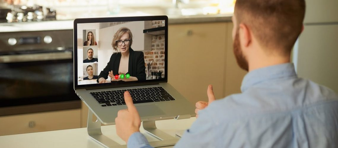 Back view of male employee who works remotely listening reports of his colleagues about a business by a video conference on a laptop computer at home. A multiethnic business team at an online meeting.